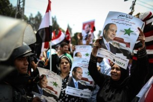 Egyptians hold portraits of now President Abdel Fattah el-Sissi as they take part in celebrations in front of the presidential palace. (MOHAMED EL-SHAHED/AFP)