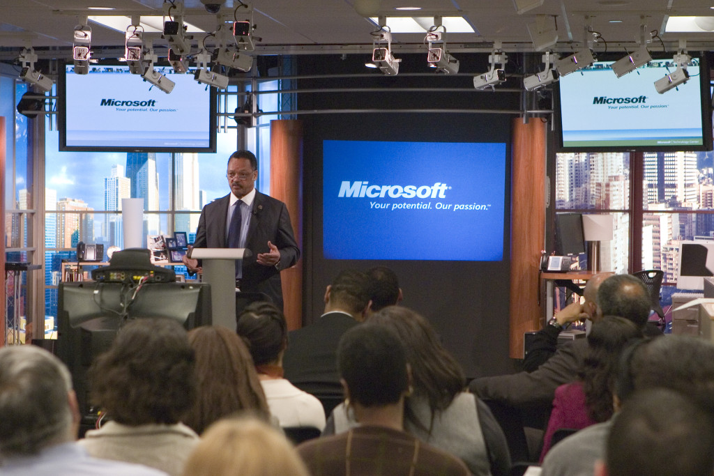 Jesse Jackson at a podium flanked by large television screens with the Microsoft logo while he speaks to an audience
