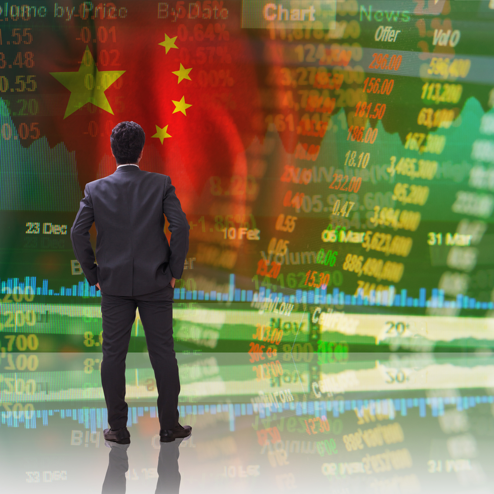 Businessman standing in front of china stock market ticker