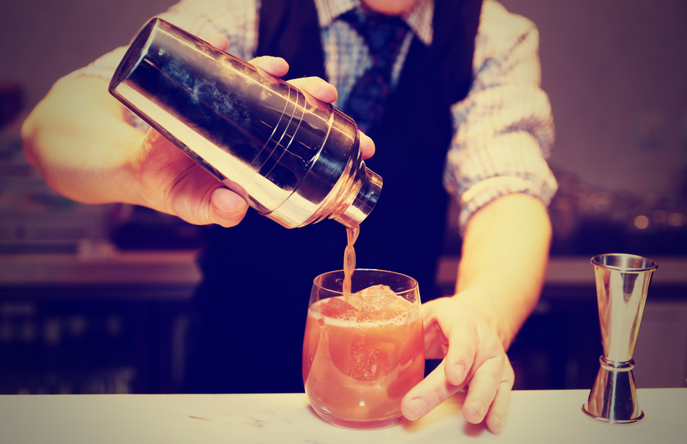 A bartender pours a cocktail.