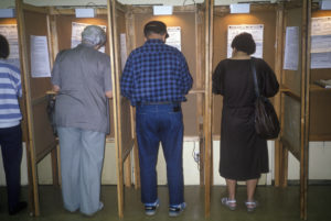 A photo of four African Americans shown from behind in their own separate voter booths.