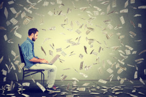 A young man sits in a chair with his laptop. There are dollar bills floating all around him.