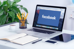 A photo of a laptop ontop of a desk. Facebook is on the screen.
