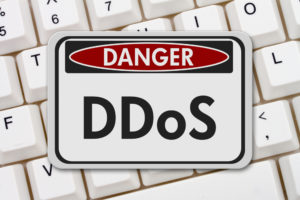 """A keyboard with a warning sign in front of it that reads, """"Danger! DDoS."""""""