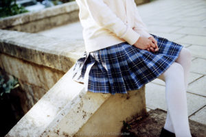 A young girl sitting on a ledge. She is wearing a skirt with stockings underneath.