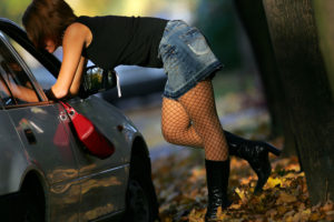 A prostitute in a short skirt leans into a car window to seal a deal.