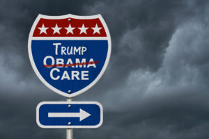 "A road sign that says ""Obama Care"" except ""Obama"" is crossed out and replaced with ""Trump."""