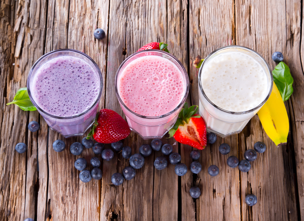 Three pretty smoothies on a wood table, surrounded by fresh fruit.