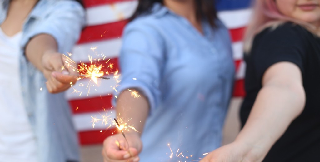 A group of women's torsos as they light sparklers in front of the American flag.