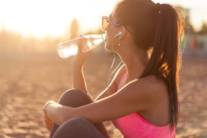 A photo of a young, attactive woman dressed in workout attire drinking water.