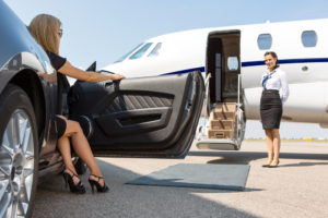 A rich woman stepping out of her card. A private plane awaits her.