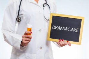 A doctor holds an ObamaCare sign in one hand and a prescription bottle in the other.